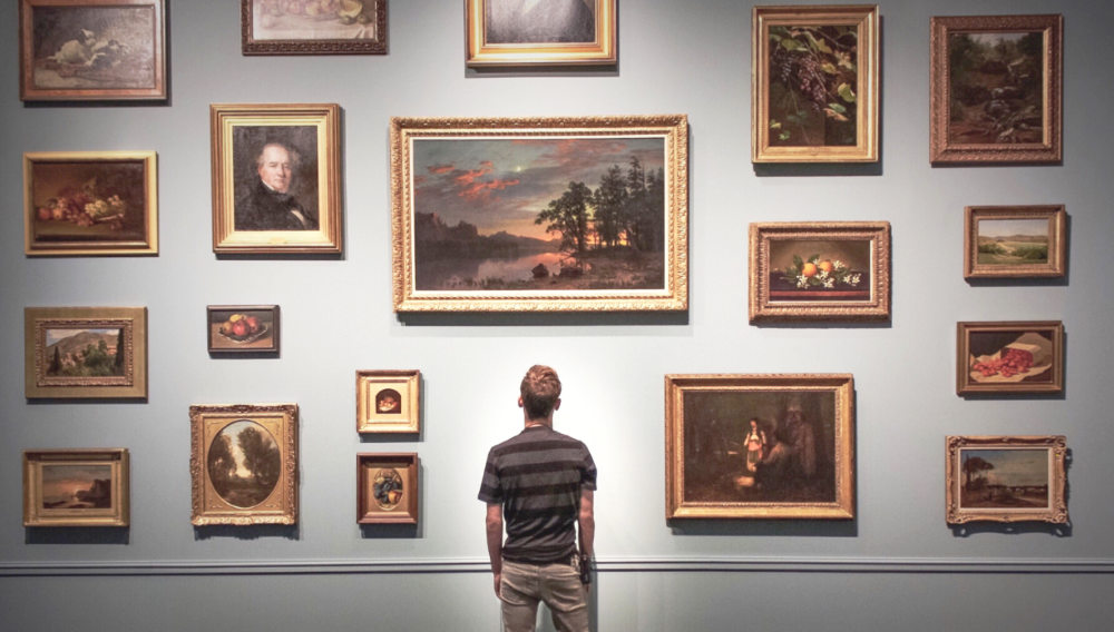 man viewing a wall of artworks